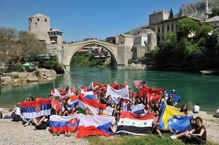 """Gruppe Jugendlicher mit Flaggen vor der """"Alten Brücke"""" in Mostar"""